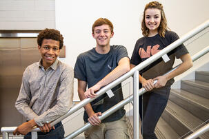 Three students standing on stairs