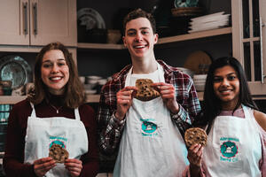 Three students holding cookies